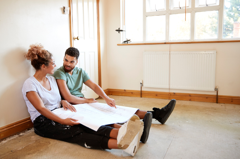 planitar couple sitting on floor looking at plans in empty 9JASQKR